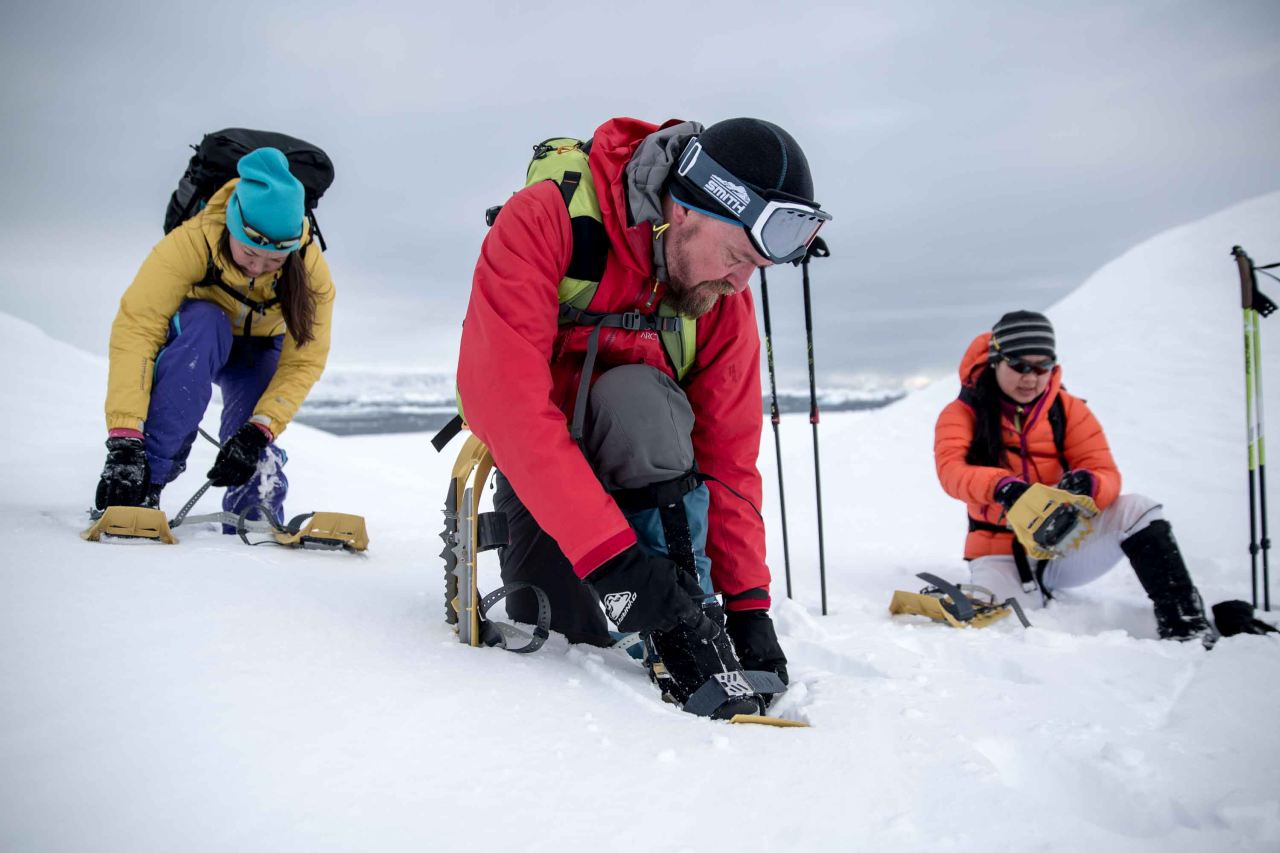 A group putting on snow shoes and getting ready for a hike in east Greenland - Icelandic Mountain Guides