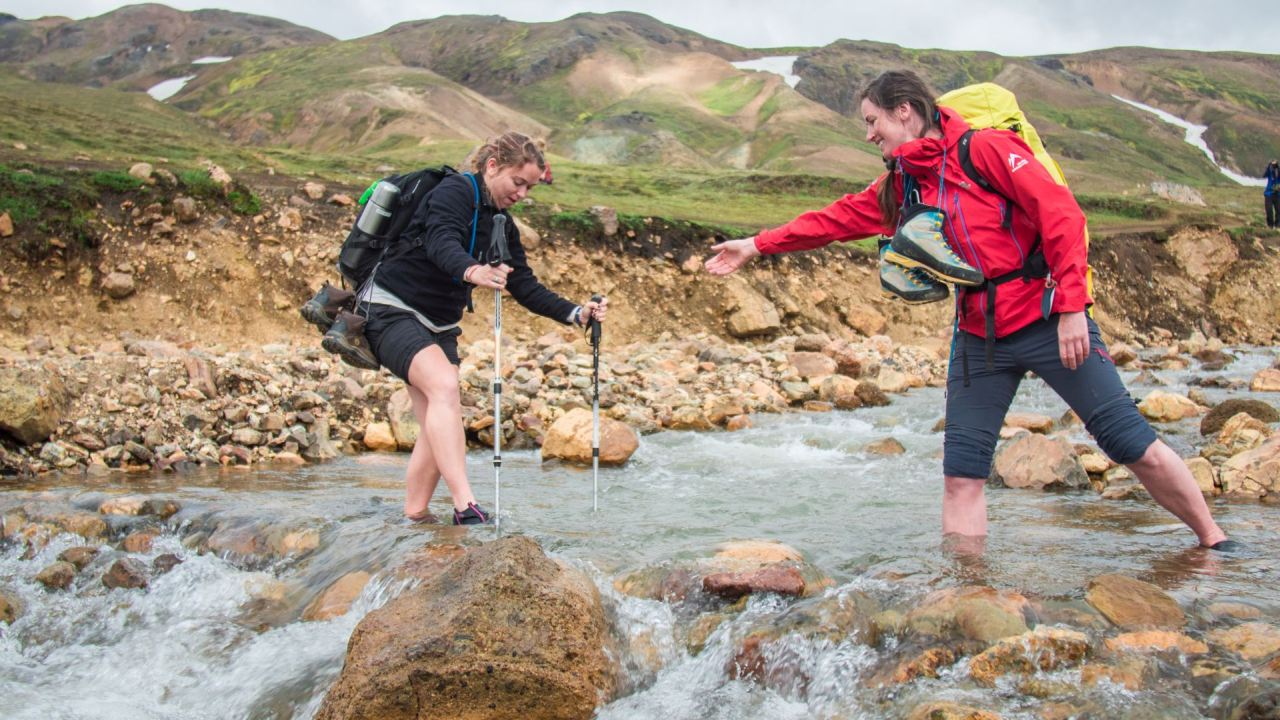 Guide helping a trekker to cross a river on the Laugavegur Trail   Icelandic Mountain Guides