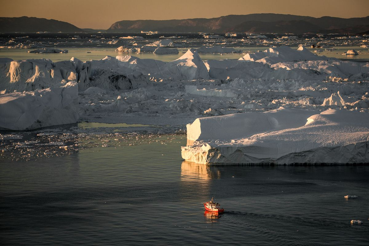A small passenger boat near huge icebergs in the Ilulissat ice fjord in Northern Greenland