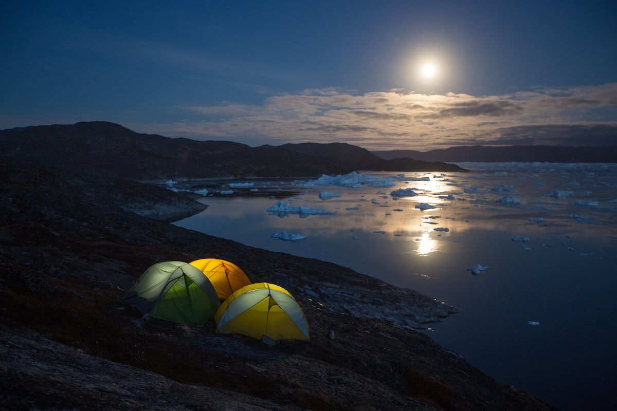 Three tents overlooking the Ilulissat icefjord under a moonlit sky