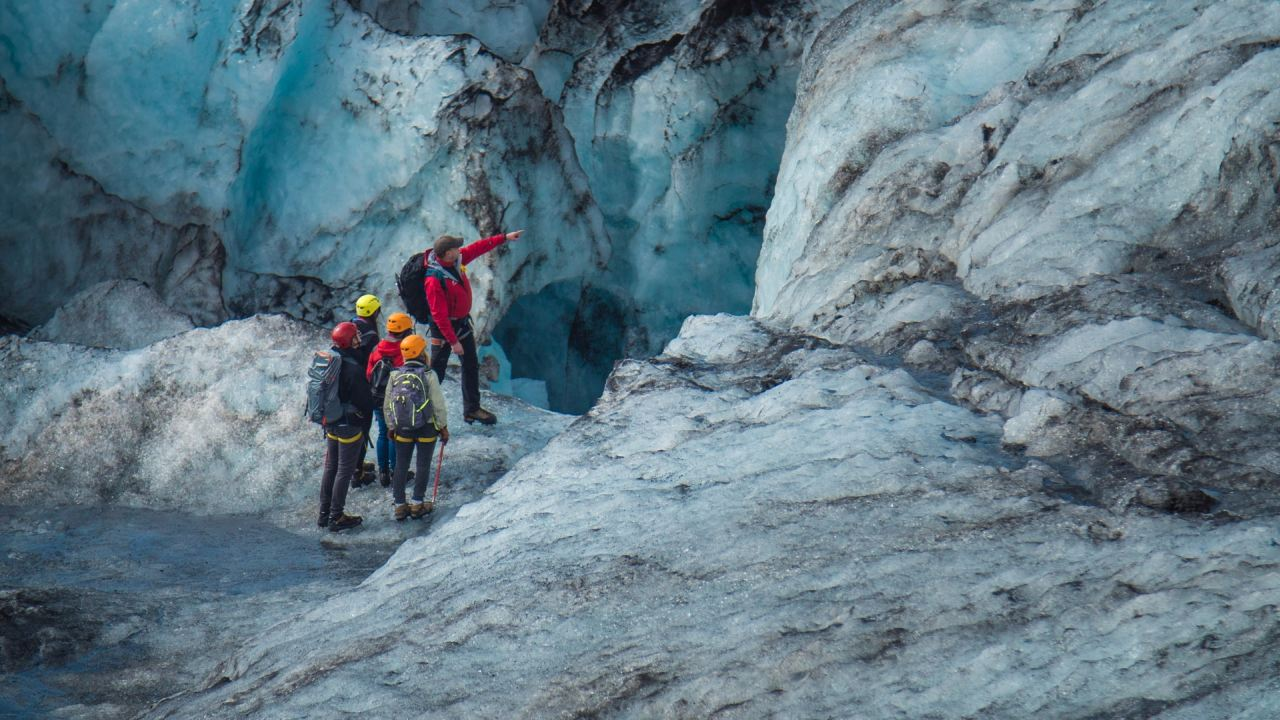 Glacier guide pointing towards a crevasse on Solheimajokull in the south coast of Iceland - South Shore Glacier Walk and Ice Climbing with Iceland Mountain Guides