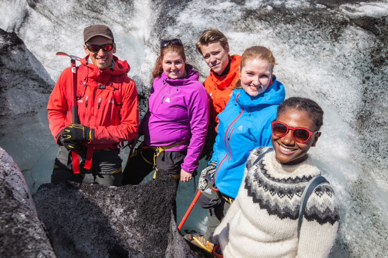 People smiling at the glacier of Solheimajokull in the south shore of Iceland - South Shore Glacier Walk and Ice Climbing with Iceland Mountain Guides
