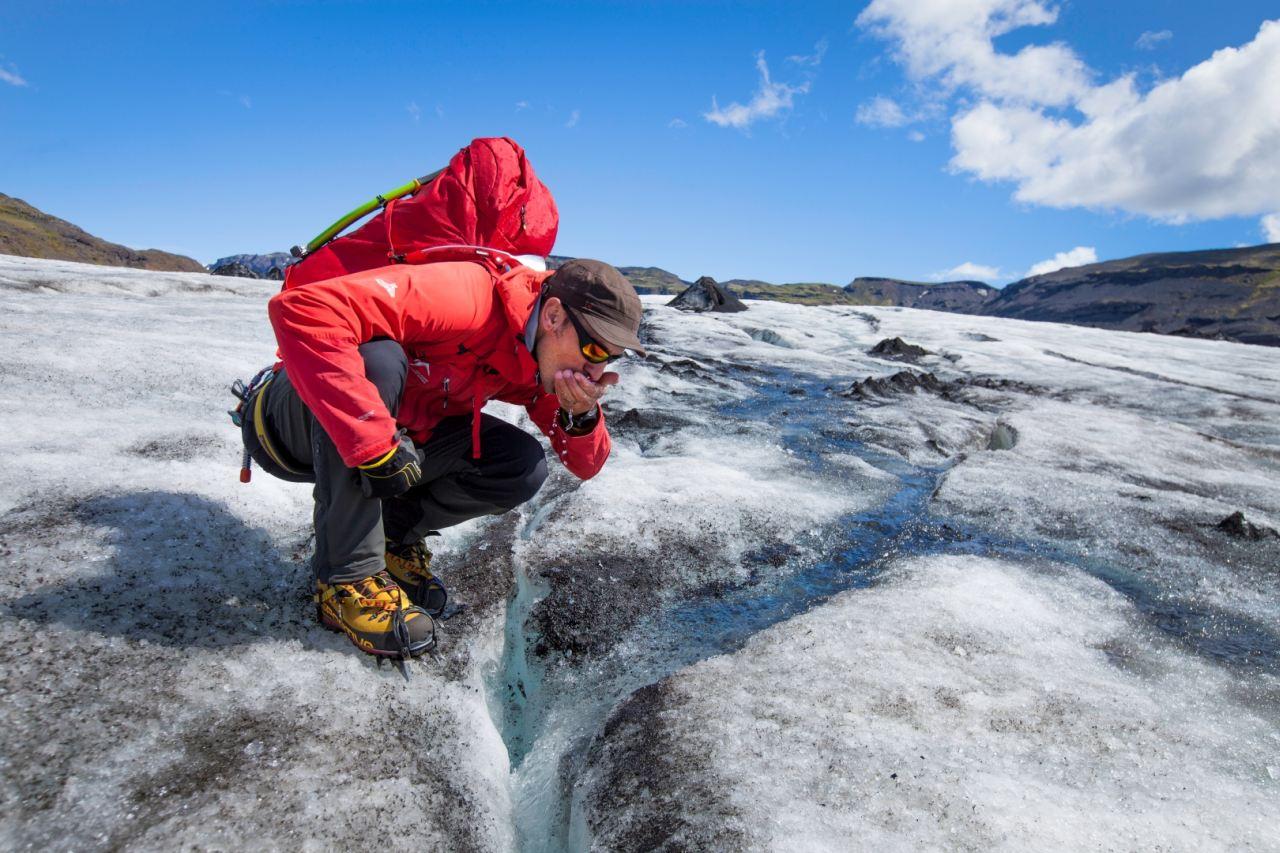 Enjoying a drink of fresh glacier water during a Glacier Walk tour on Sólheimajökull glacier