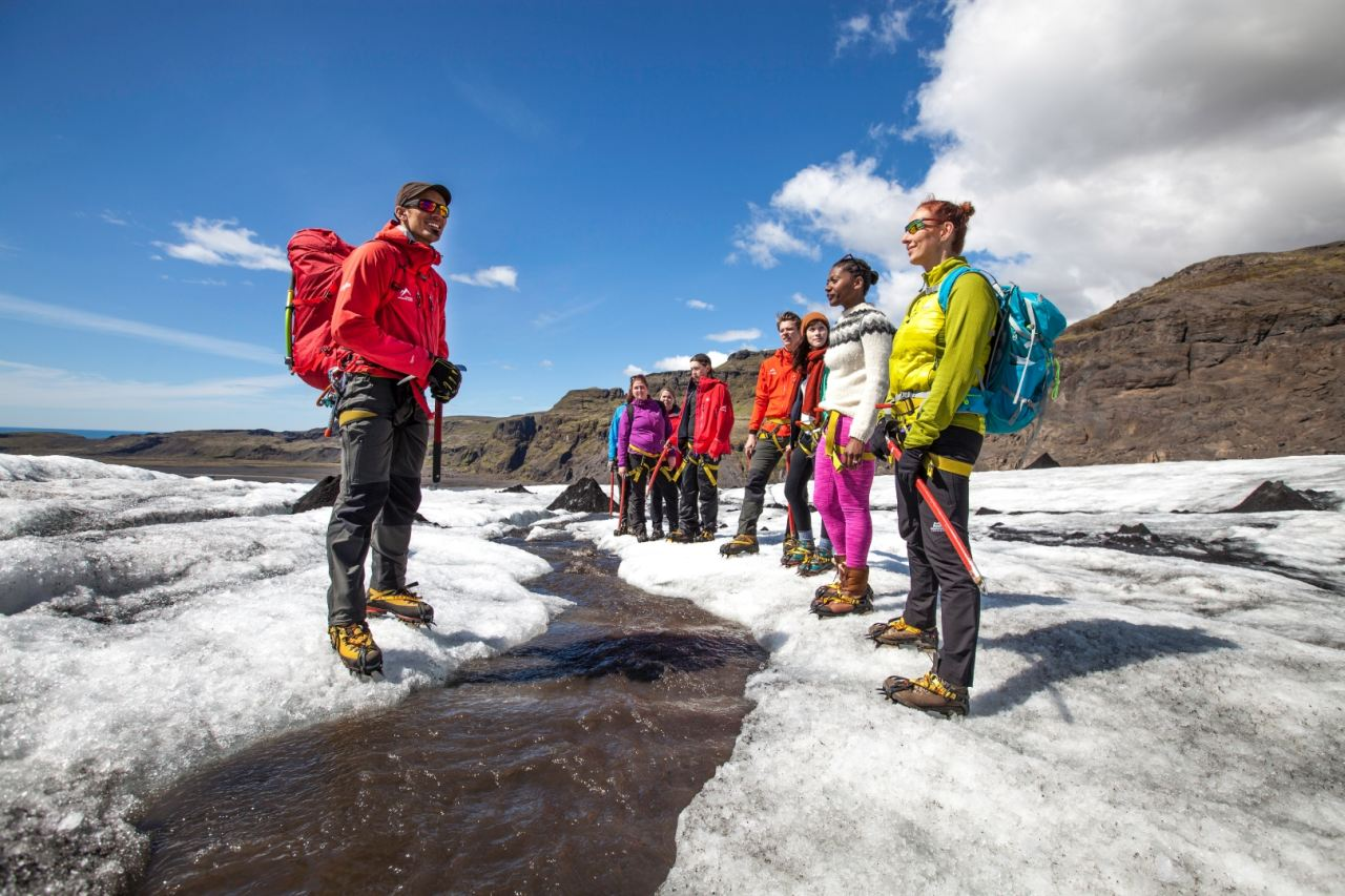 Guide from Icelandic Mountain Guides talking about the fresh glacier water on Sólheimajökull glacier during a glacier walk tour