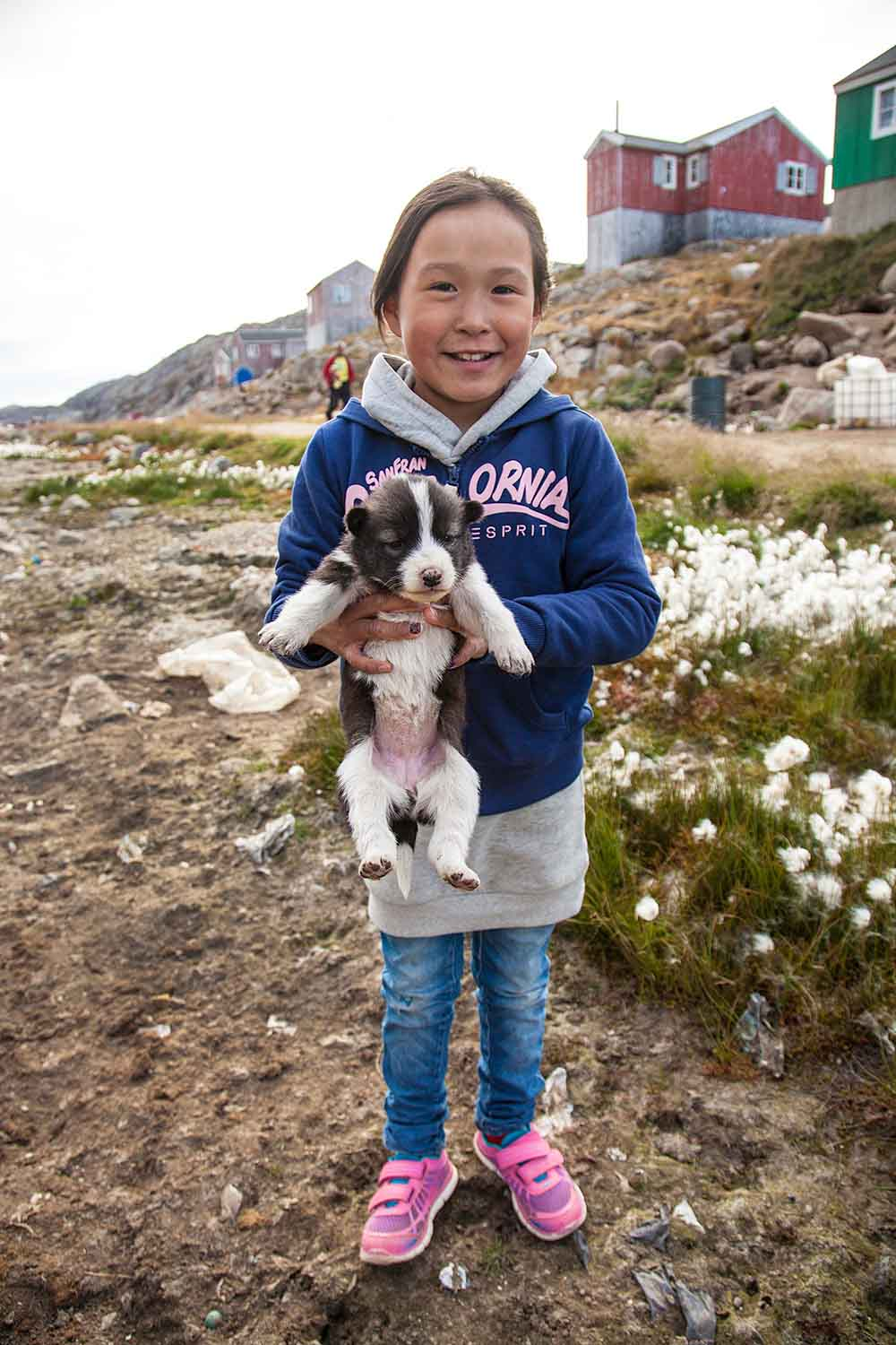 Greenlandic girl with husky puppy