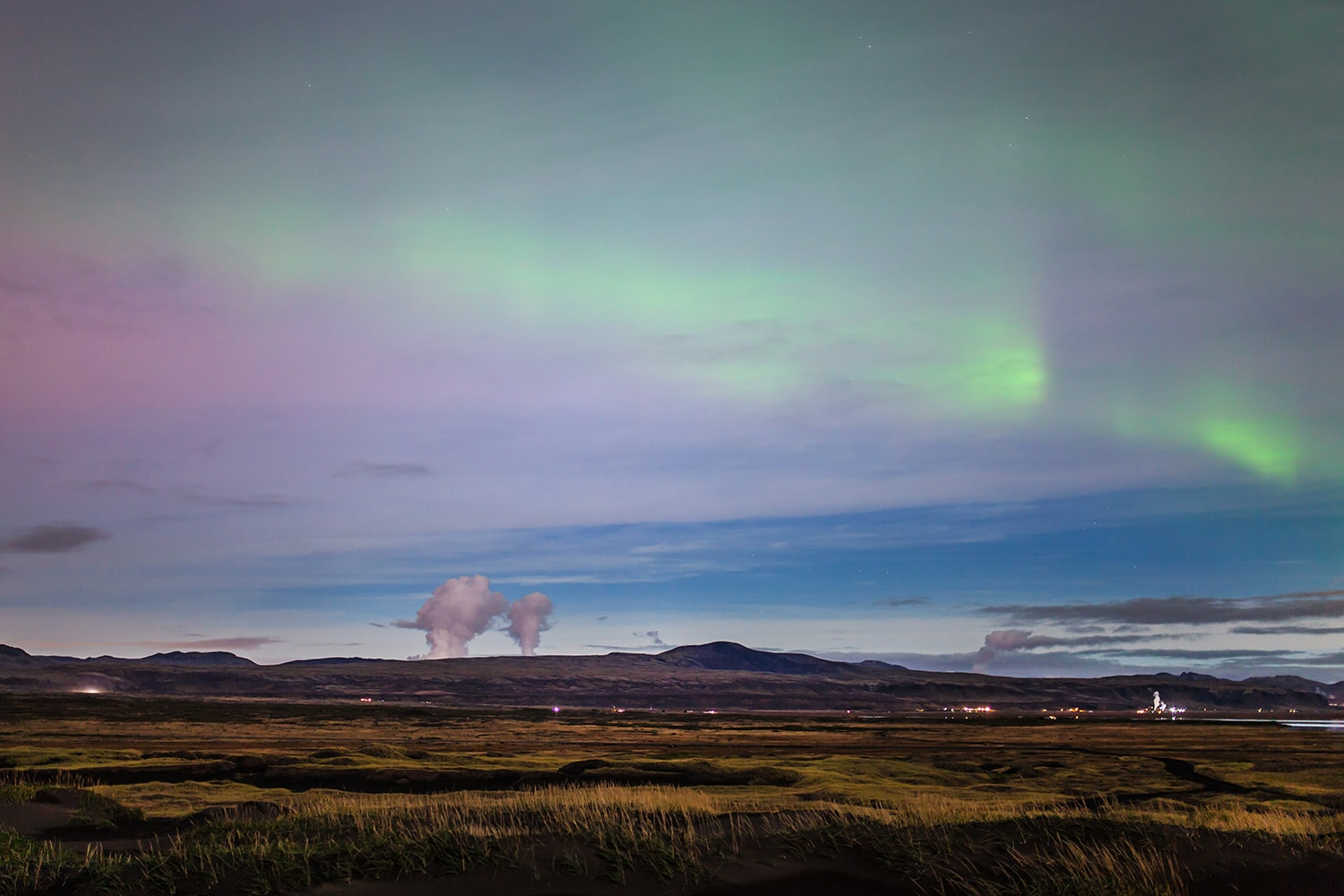 Northern lights and steam from a nearby geothermal area