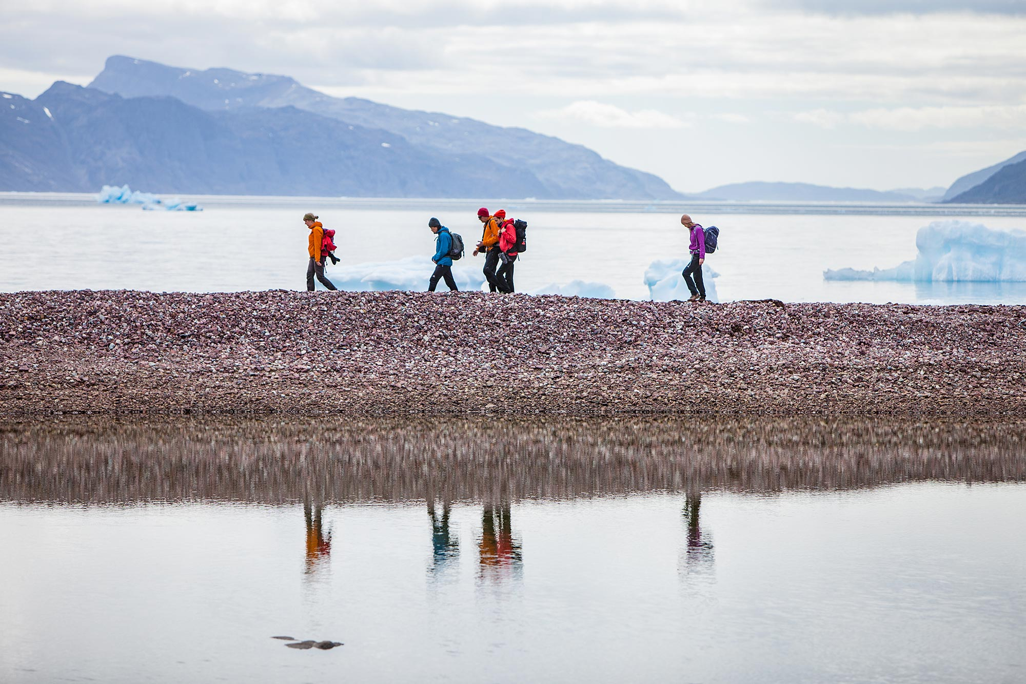 hikers in beautiful landscapes, icebergs and fjords reflected