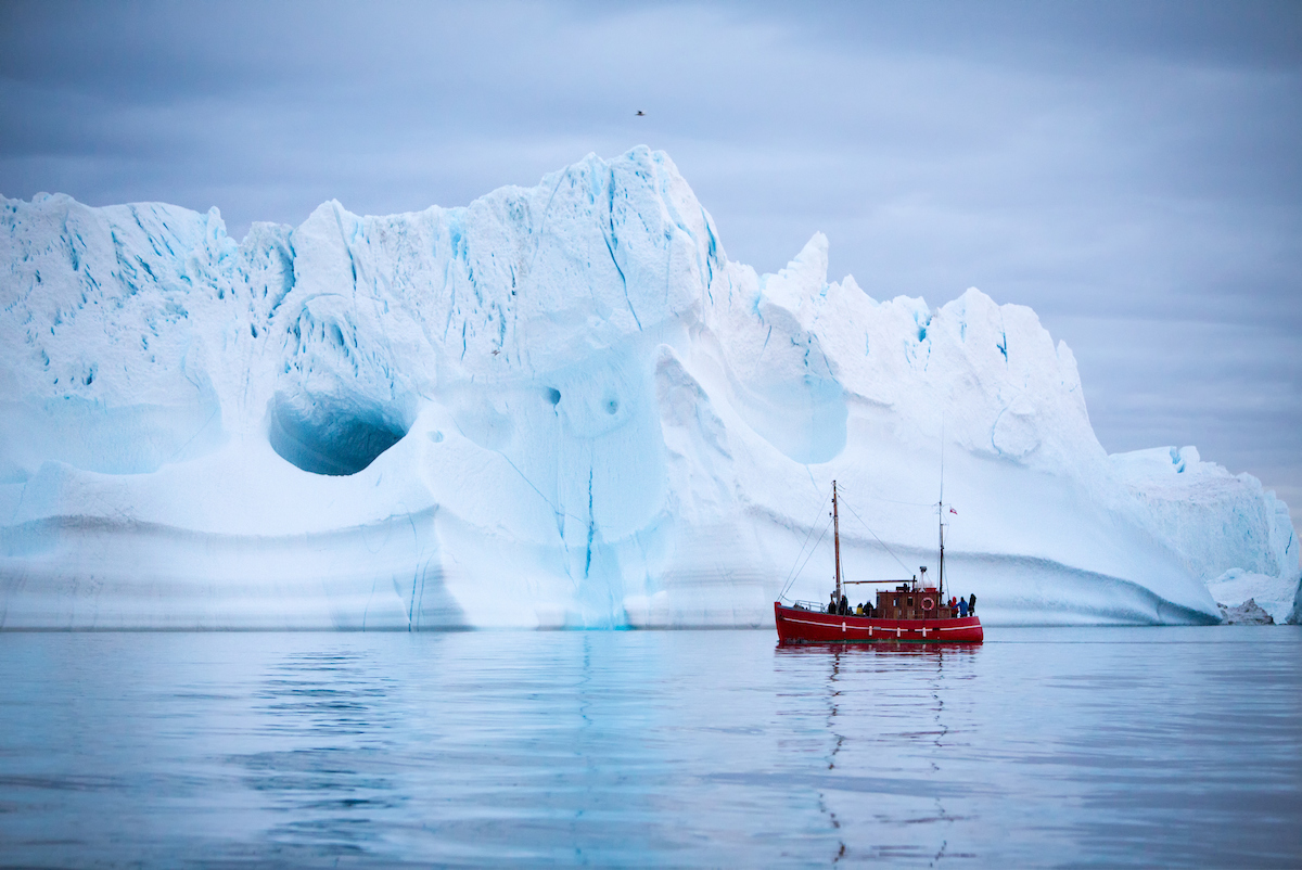 A Boat Tour Sailing By A Giant Iceberg